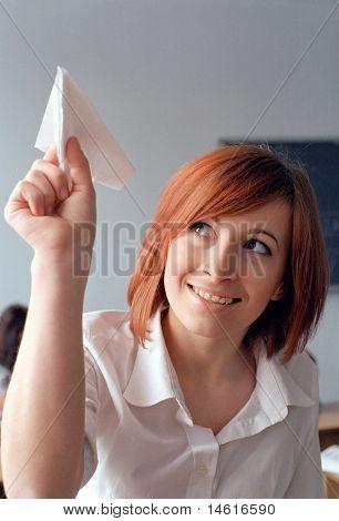 redhead schoolgirl run a paper airplane