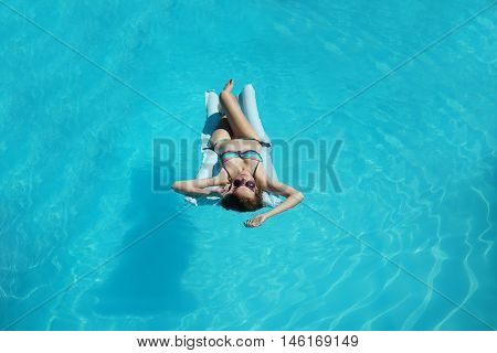 Young woman with sexy beautiful body in bikini and sunglasses relaxing during suntan laying on air mattress on background of blue water of swimming pool in summer