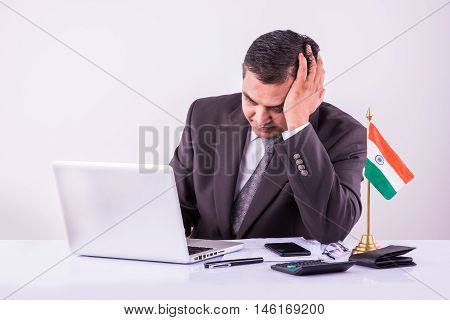 stressed indian businessman holding head with one hand while filling tax form or accounting on laptop
