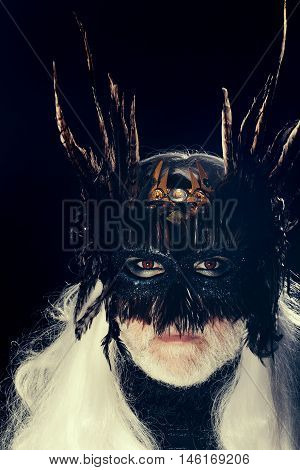 Male bearded face with long white hair and ominous sight in vintage decorative masque with dark brown feathers for fancy ball on black background studio