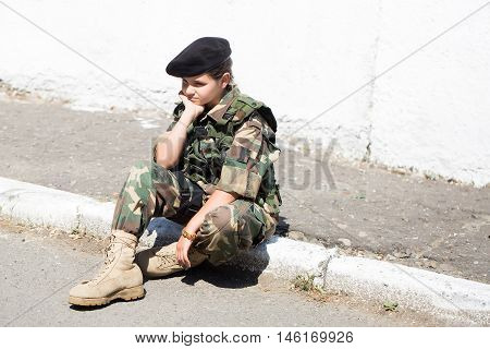 Young girl child with pretty sad thoughtful face in army camouflage ammunition and black beret sitting on stone ground outdoor