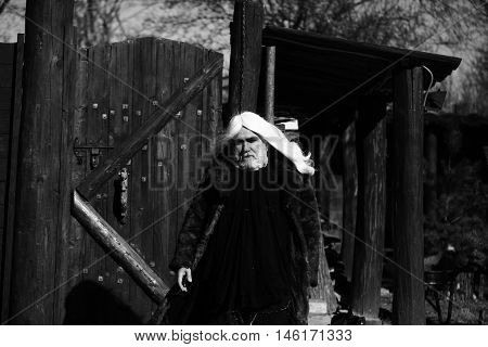 Druid old bearded man with long white hair and beard on serious face in fur coat sunny day outdoor on wood background black and white