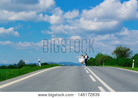 young wedding happy couple of sexy girl with brunette hair and pretty face in white bride dress and handsome man in black groom suit running on road way on cloudy blue sky background copy space