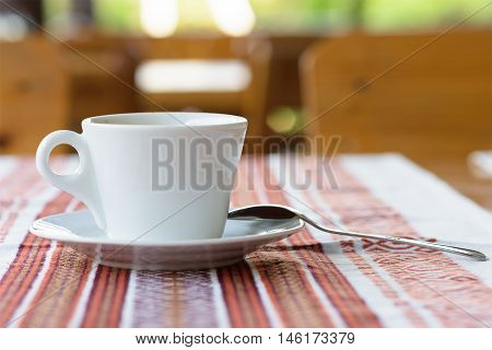 Photo of white cup of coffee on a traditional restaurant table in Moldova, tablecloth with ornaments, shallow focus