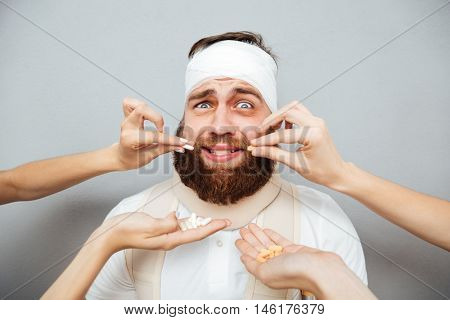 Frightened scared bandaged man taking pills from doctors hands over gray background