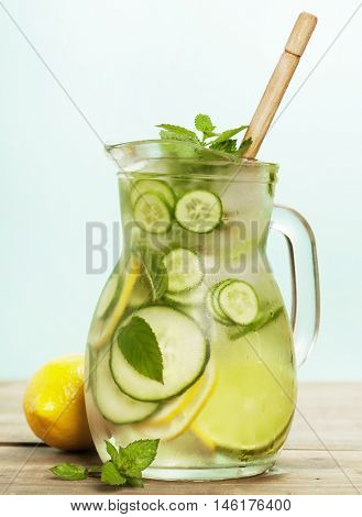 Infused water with cucumber, lemon, lime and mint on blue background
