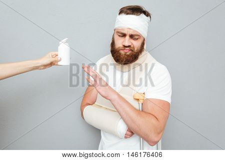Sad bandaged young man with crutches refuses to take pills over gray background