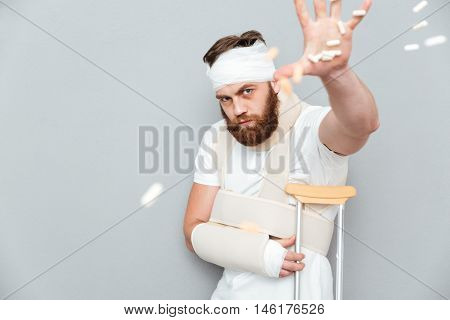 Angry irritated bandaged bearded man catching tablets with hand over gray background