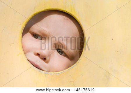 Closeup portrait of cute little toddler boy looking into yellow wooden frame at playground. Curiosity exploration and leaning. Activities for children outdoors. Preschool daycare. Small boy playing