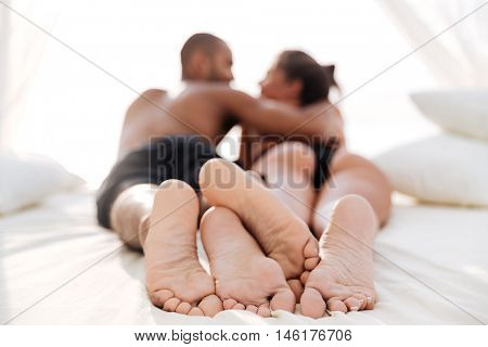 Image of happy multiracial couple laying at the white beach bed and embracing