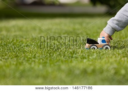 Closeup of child's hand playing with toy cay on the green grass in the park. Toddler boy playing with small car. Daycare and nursery. Outdoors. Childhood and lifestyle concept. Activities for children