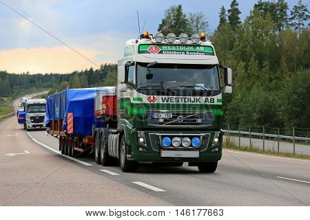 ORIVESI FINLAND - SEPTEMBER 1 2016: Volvo FH semi truck of Westdijk AB hauls wide load in convoy along scenic road in Central Finland.