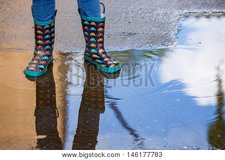 Kid boy in funny rubber boots standing in the puddle in the street after rain. Pair of colorful rubber boots in a big puddle with refclections. Boy having fun after rain. Outdoor.