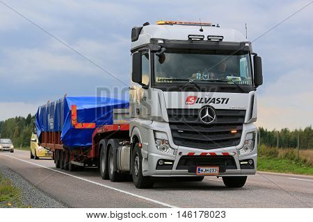 ORIVESI FINLAND - SEPTEMBER 1 2016: Silver Mercedes-Benz Actros 3351 semi truck hauls wide load accompanied by an escort vehicle in Central Finland.