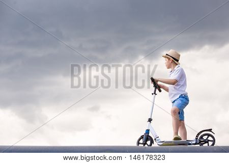 Cute kid boy riding his scooter into cloudy sky - happiness childhood freedom speed and active lifestyle concept - smiling boy in straw hat on scooter in air over grey rainy sky.