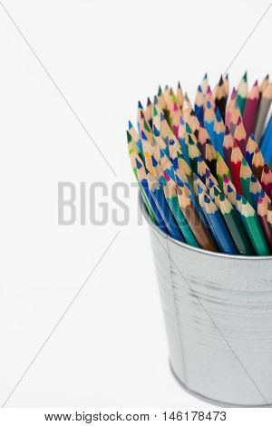 Various colour pencils organized in a can. Stack of colored pencils in a tin can on white background.