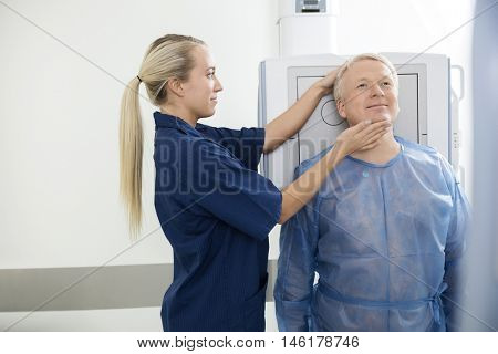 Radiologist Adjusting Head Of Mature Patient Before Taking Xray