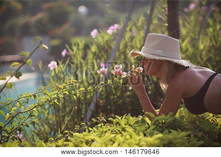 babe in a bathing suit is smelling flowers