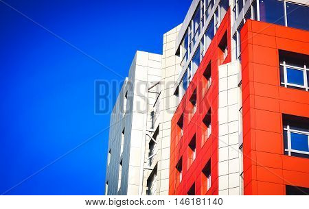 Part of the facade of a modern building with red walls square windows the blue mirrored glass. Architecture in a modern style and high-tech on a bright sunny day