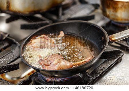 Duck legs frying in a pan, restaurant kitchen