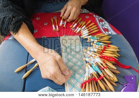 Woman hands are making bobbin lace with threads