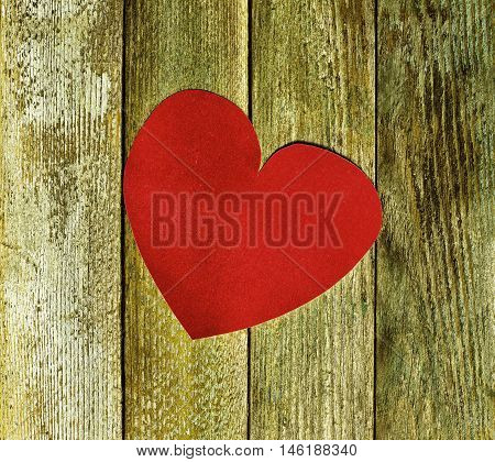 Big red heart velvet paper on old wooden boards close up. The concept of love Valentine's day. tinted photo