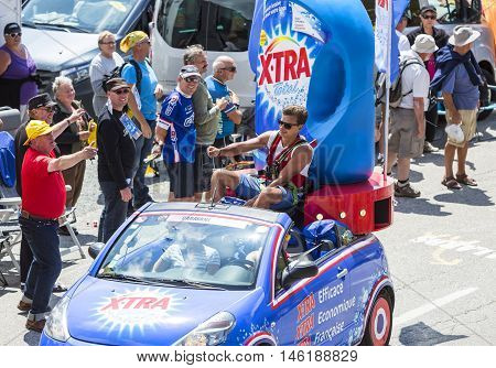 Col du Glandon France - July 23 2015: Young man throwing promotional stuff from X-tra Total vehicle during the passing of the Publicity Caravan on Col du Glandon in Alps during the stage 18 of Le Tour de France 2015. X-tra Total is a good detergent for al