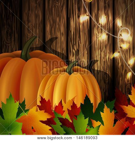 autumn leaves and two orange pumpkins with patio lights on wooden texture. Could be used for your Thanksgiving greetings