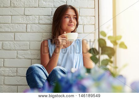 Young modern girl enjoyed the moment of relaxation and drinking a cup of aroma coffee on the window-sill in a calm and peaceful atmosphere on a gorgeous day