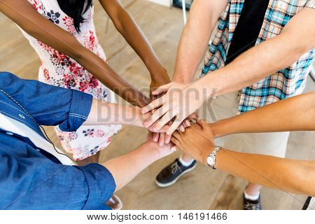 Top view of young people putting hands together