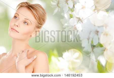 beauty, people and bodycare concept -beautiful young woman face and hands over natural spring cherry blossom background