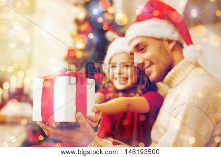 holidays, christmas, family and happiness concept - close up of father and daughter with gift box