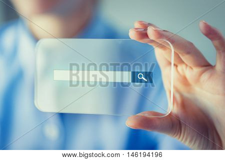 business, technology, network, web and people concept - close up of woman hand holding and showing transparent smartphone with browser search bar on screen