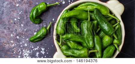Food and drink, still life, moody concept. Raw green peppers pimientos de padron wth sea salt traditional spanish tapas on a black rusty table. Selective focus top view flat lay