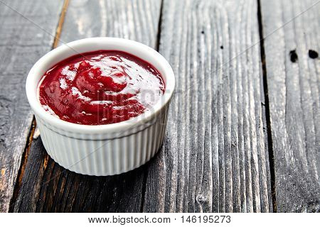 Delicious homemade cranberry sauce in a white bowl. Berry confiture on dark wooden table.Perfect traditional sweetness for the cup of tea., turkey and chicken. Close up shot