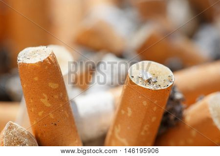 Close-up of big pile of put out cigarettes in an ashtray. Smoking smoker addiction health hazard lung cancer concept.