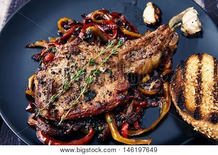Delicious, juicy, hot club steak veal on the bone. Meat Prime rib with sauteed bell peppers and onions, decorated with two sprigs of thyme on a black plate with a toasted bun and garlic. Main dish