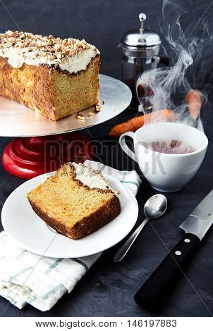 A slice of carrot cake with butter cream and crumbled nuts on a white saucer. Next to it a cup of hot tea, dessert spoon, knife and cake stand with the cake on it. Behind blurred kettle and carrots