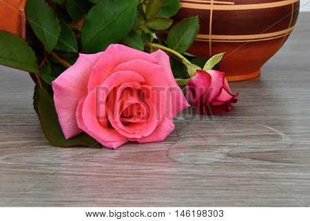 Capsize flower vase with roses. Water leaked out of a vase. The vase is a wooden base.