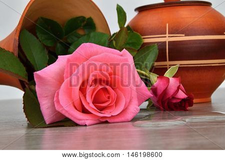 Capsize flower vase with roses. Water leaked out of a vase. Vase on a wooden base.