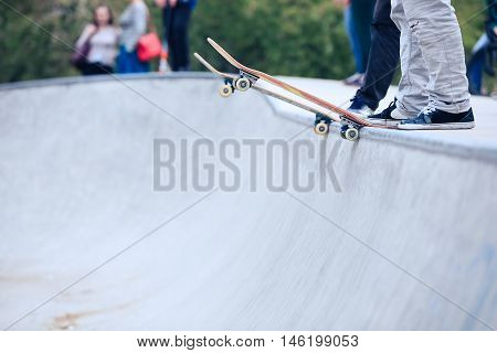 Skateboarder standing on a ramp in skate park ready to ride skate board and do tricks. Concrete outdoor park focus on skateboard feet and shoes