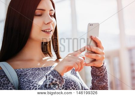 Smiling Young Girl Using Modern Dual Camera Smart Phone
