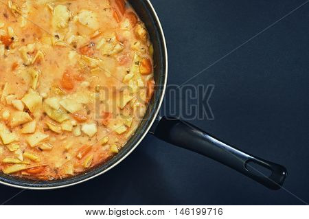 Cooked vegan green beans stew in black pan on dark background. Top view with copy space