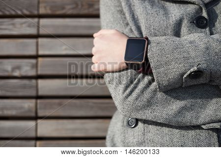 Woman in grey coat wearing modern smart wrist watch. This person is always connected to social media and internet even sitting on the bench.