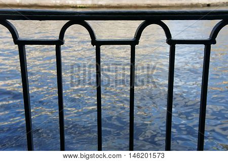 metal railing on the promenade, view of water