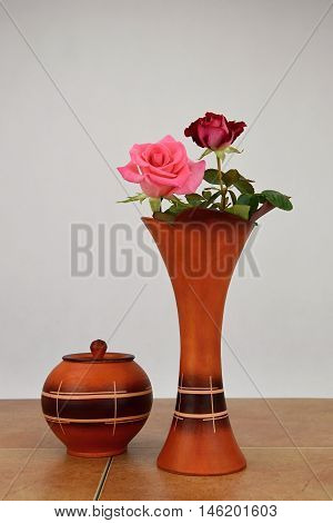 Two roses in a ceramic vase for flowers. The vase stands on ceramic tiles.