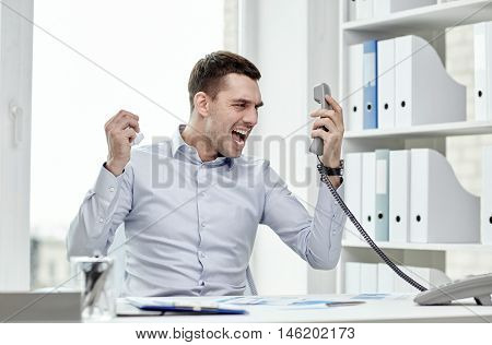 business, people, emotions, stress and communication concept - furious businessman calling on phone in office