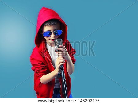 Little boy singing with microphone on blue background.