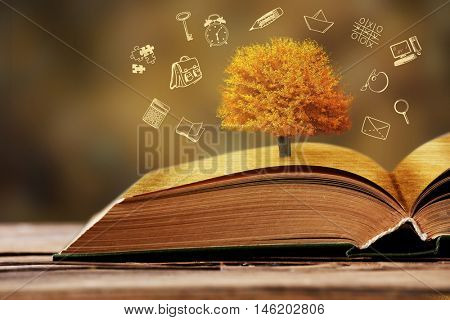 Book with tree on wooden table. Icons on blurred background.