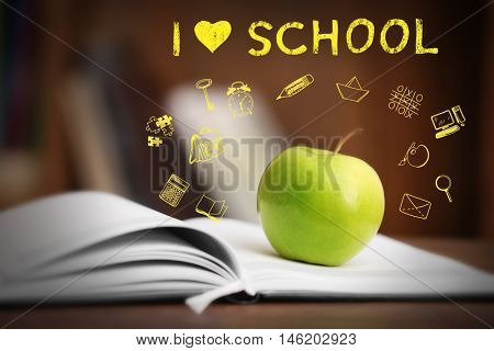 Book with apple on wooden table. Text I LOVE SCHOOL and icons on blurred background.